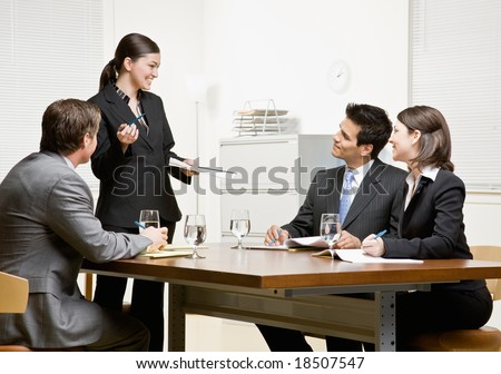 Co-workers listening to supervisor explain issue in conference room - stock photo