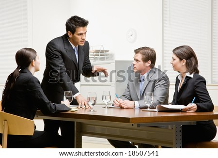 Co-workers listening to supervisor explain problem in conference room - stock photo