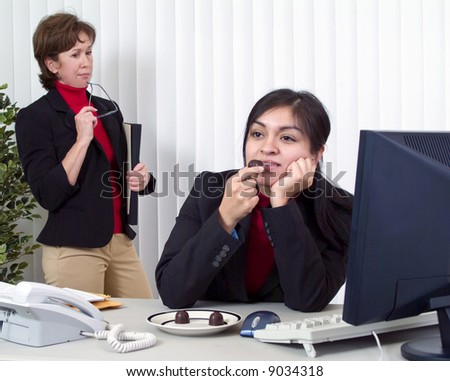 Co-workers on the job, one dreamily enjoying chocolate, the other annoyed by what she sees. - stock photo