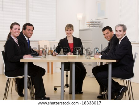 Co-workers sitting at conference table in conference room having meeting - stock photo