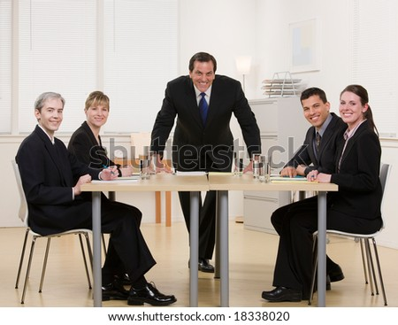 Co-workers sitting at conference table in conference room having meeting lead by supervisor - stock photo