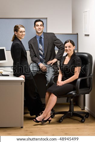 Co-workers sitting in office cubicle - stock photo