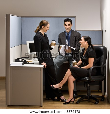 Co-workers talking in office cubicle - stock photo