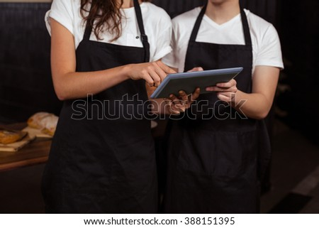 Co-workers using tablet at the coffee shop - stock photo