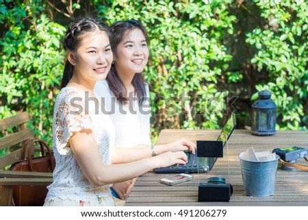 Co-working business green garden two asian women discussing of work on wood table outdoor