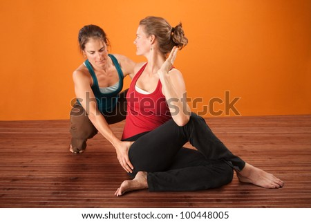 Coach and student in yoga workout clothes - stock photo