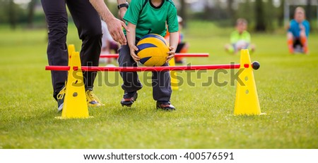 Coach and young boy exercising with ball on a green grass - stock photo