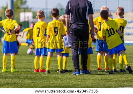 Coach and youth soccer reserve players watching football match. Coach giving young soccer team instructions.  Coach briefing. Soccer football background. - stock photo