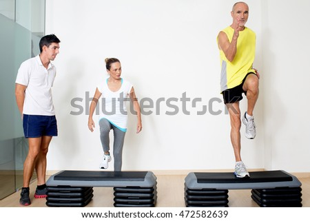 Coach controlling step exercise of seniors