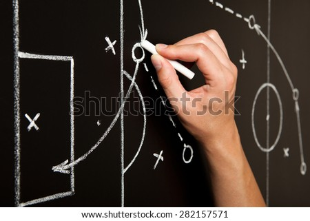 Coach drawing a football game tactics with white chalk on blackboard. Soccer coach explaining game strategy. - stock photo