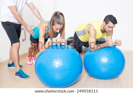 Coach helping with fitness ball exercise - stock photo