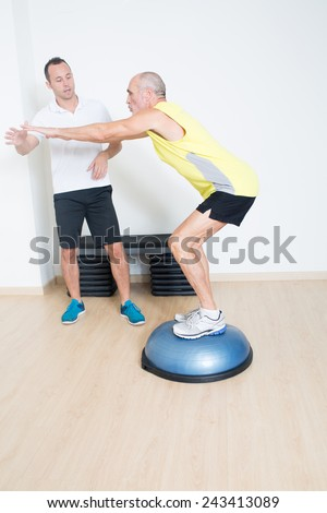 Coach helps senior with bosu exercise - stock photo