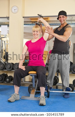 coach instructing smiling woman exercising with dumbbells in gym - stock photo
