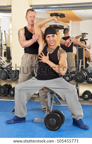 coach instructing young man while exercising with dumbbells in gym - stock photo