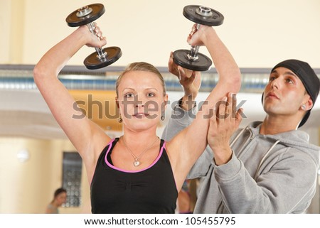 coach instructing young woman exercising with dumbbells in gym - stock photo