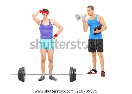 Coach motivating a nerdy guy to exercise, with a megaphone isolated on white background - stock photo