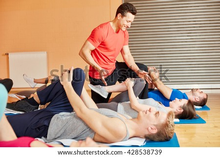 Coach motivating his pilates group with healthy stretching - stock photo
