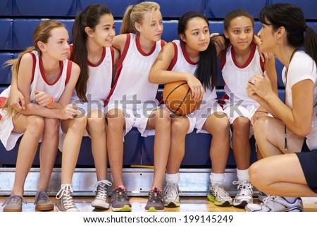 Coach Of Female High School Basketball Team Gives Team Talk - stock photo