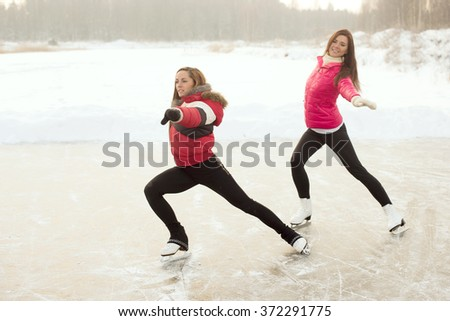 Coach of figure skating with apprentice practiced at the frozen lake in the winter - stock photo