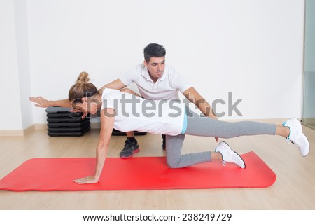 coach showing flexibility exercise to an elder woman - stock photo