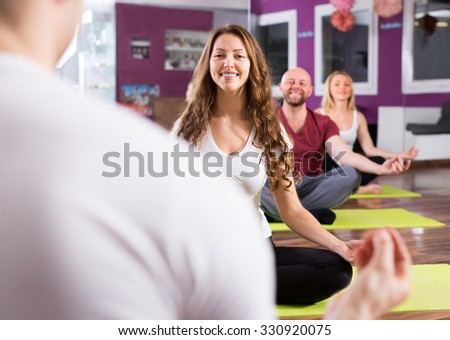Coach showing to adult russian learners new yoga posture at class - stock photo