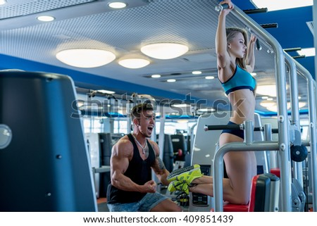 Coach supports woman pulls up on horizontal bar - stock photo