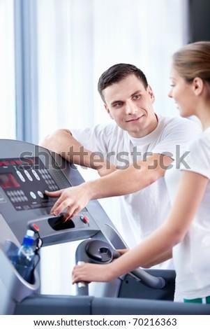 Coach with the girl runs on a treadmill - stock photo