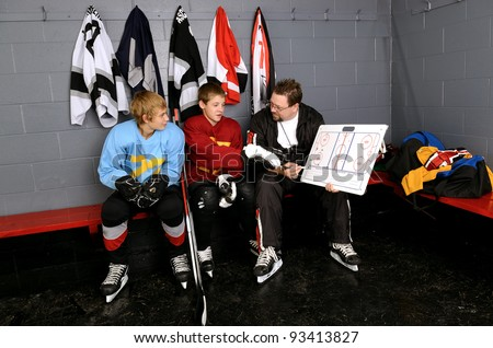 Coaching Teenage Hockey Players in Locker Room - stock photo