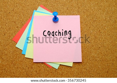 Coaching written on color sticker notes over cork board background. - stock photo