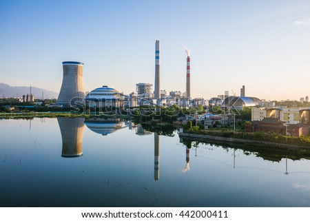 Coal-fired power plant reflection in a lake with blue sky, industry landscape