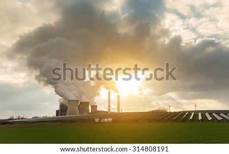 Coal-fired power plant with solar enegerie and windmills and cloudy sky and sunlight - stock photo