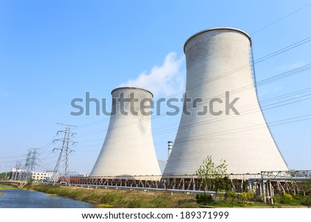 coal fired power station with cooling towers releasing steam into atmosphere