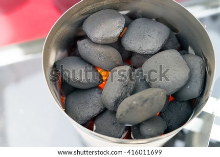 coal lighter on a charcoal grill / coal lighter - stock photo