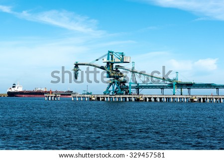 Coal loading belt with crane and ship - stock photo