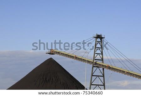 Coal Loading Conveyor Belt and a Pile of Coal at a Coal Mine - stock photo