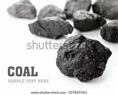Coal lumps spilled on white background with copy space - stock photo