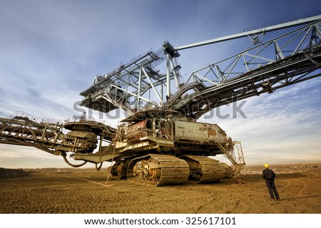 Coal mine worker with a helmet on his head is standing in front of huge drill machine and looking at it. Rear view. - stock photo