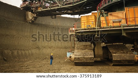 Coal mine worker with a helmet on his head standing in front of huge drill machine and looking at it. Rear view. - stock photo