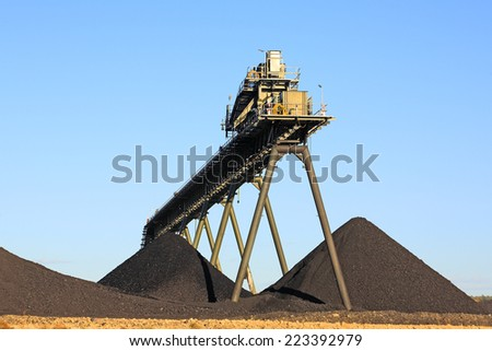 Coal Mining Conveyor Belt and piles of coal with a blue sky background. Australia - stock photo