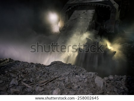 Coal mining harvester while working at a depth of about 700 meters underground - stock photo