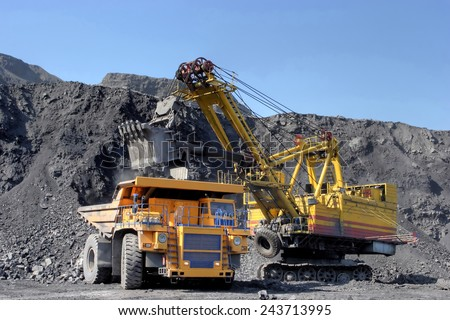 Coal mining. The dredge loads the truck coal. - stock photo