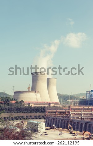 coal power plant against sun with chimneys and huge fumes - stock photo