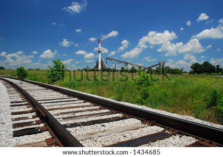 Coal Power Plant and Railroad Tracks, Green Grass, Blue Sky, and Clouds - stock photo