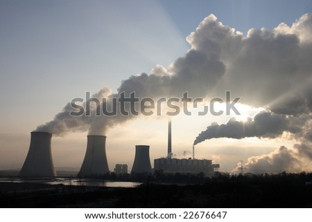 Coal power plant polluting the planet, several thin and several thick chimneys smoking towards the sky