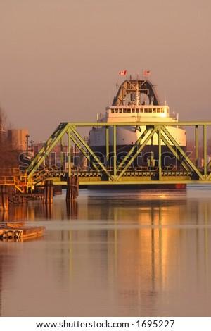 Coal ship at RR bridge,at dawn - stock photo