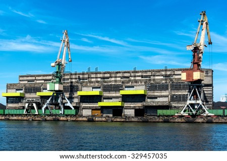 Coal storage building and train unloading cranes - stock photo