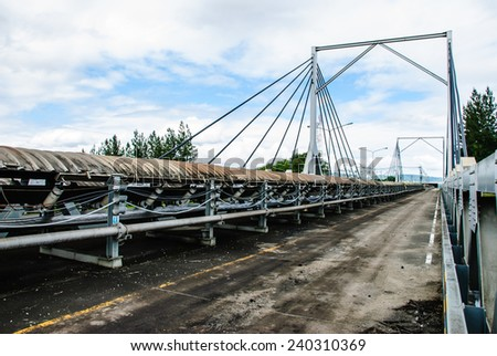 Coal was transported by coveyor belts from open-pit mine to the stock pile. Conveyor bridge was used when conveyor belts cross a road, Mae Moh mine, Lampang, Thailand. - stock photo