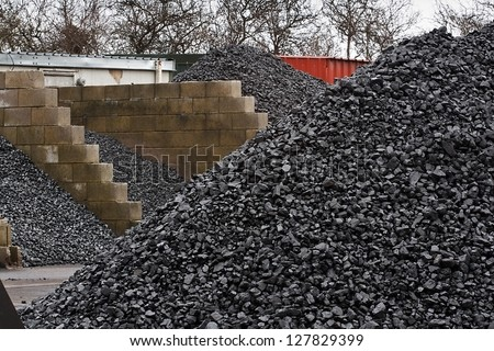 Coal yard with supply in heaps for domestic use - stock photo