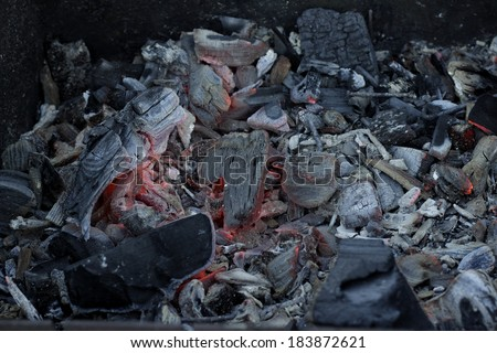 Coals on fire in ashes - stock photo
