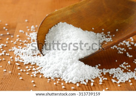 Coarse grained salt on a wooden scoop - stock photo